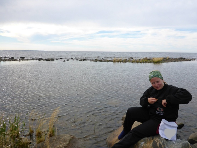 A person sitting on a rock with her lunch bag next to the water.