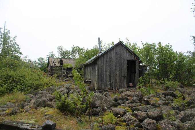 Two, almost fallen wooden buildings and very rocky yard.