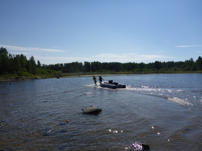 Two persons dragging a rubber boat to the shore in very shallow water.