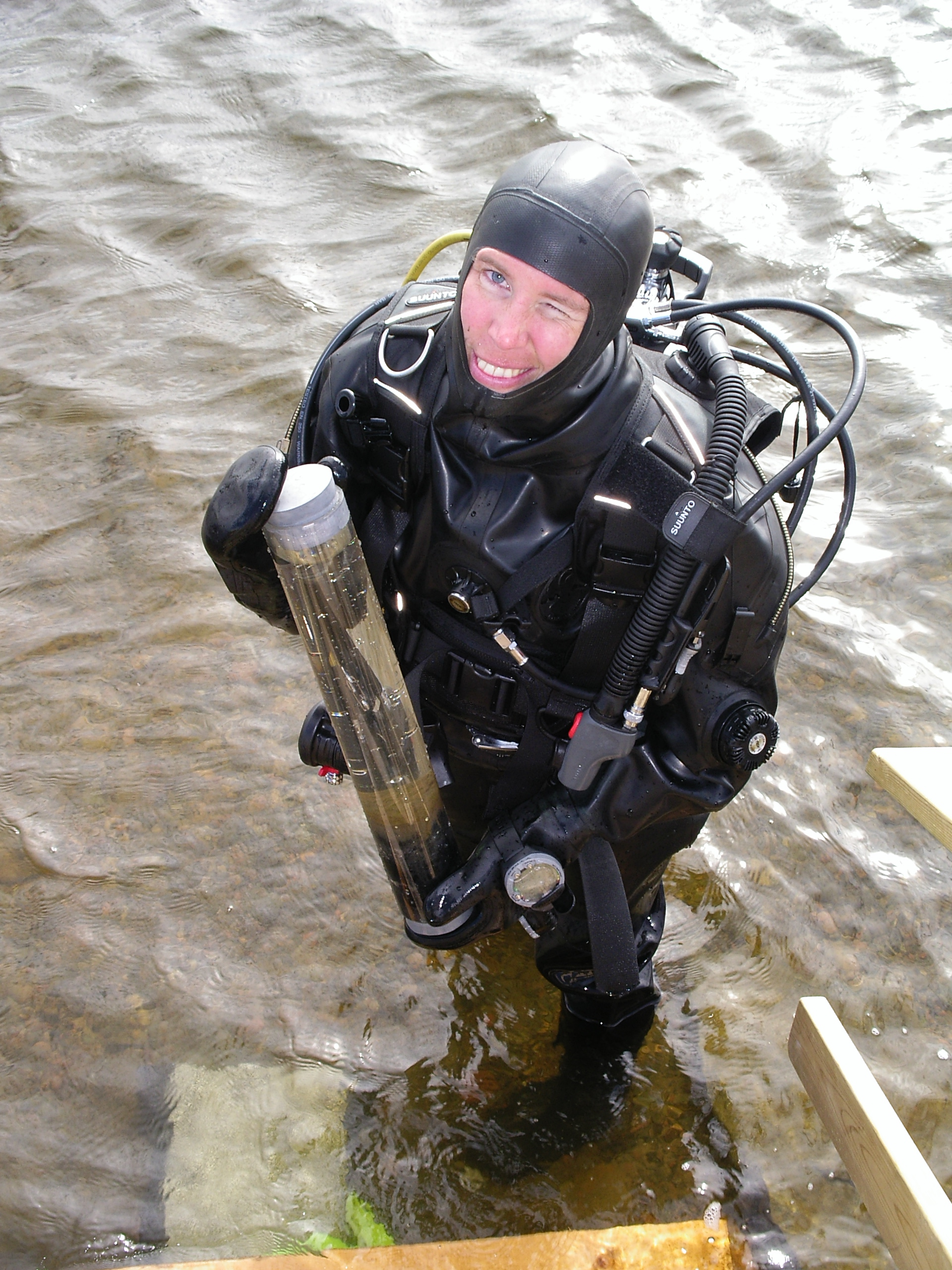 Essi Keskinen with a sampler, standing in shallow water in full diving gear.