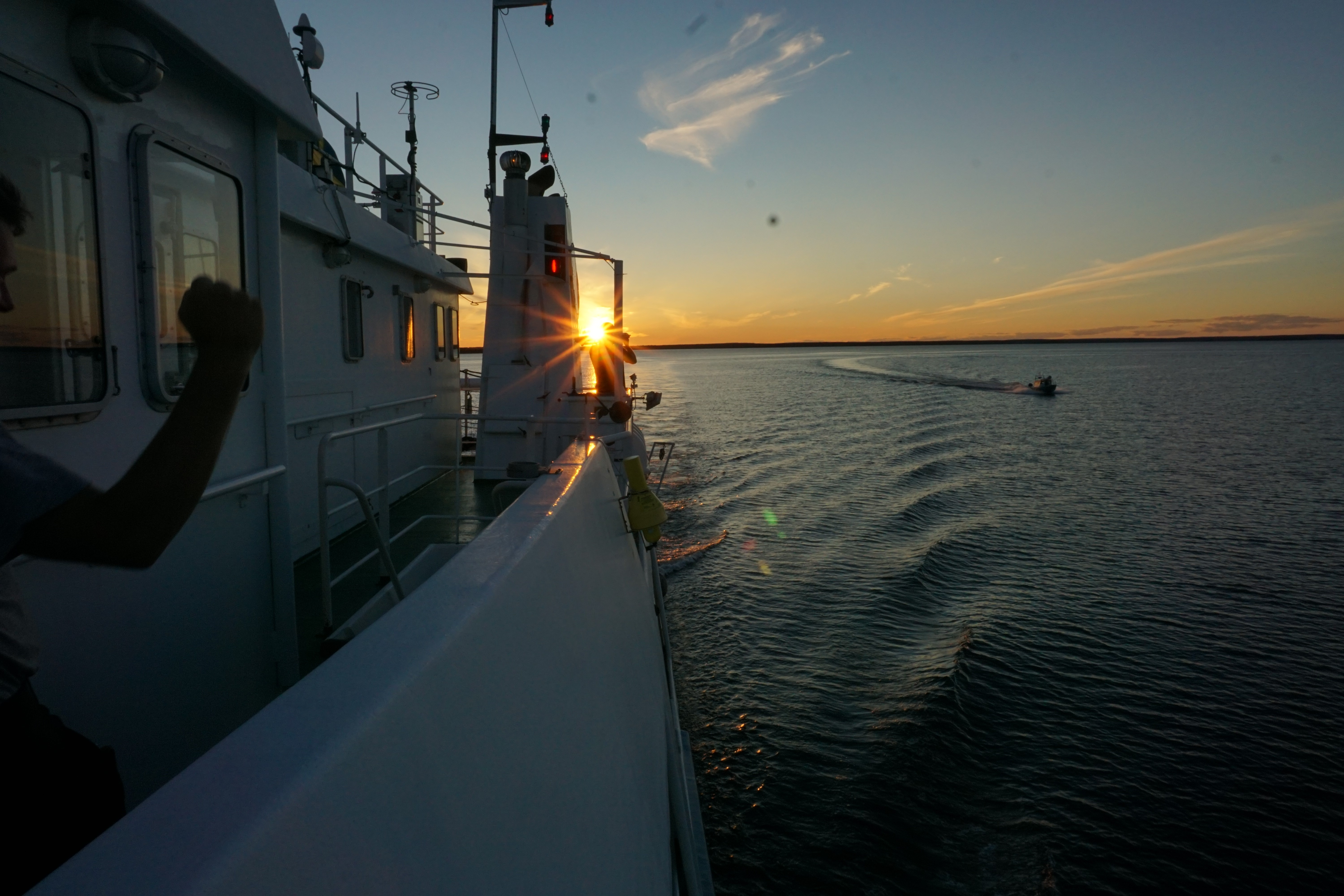 A ship and a person on board flexing arm. Sunset on the background.