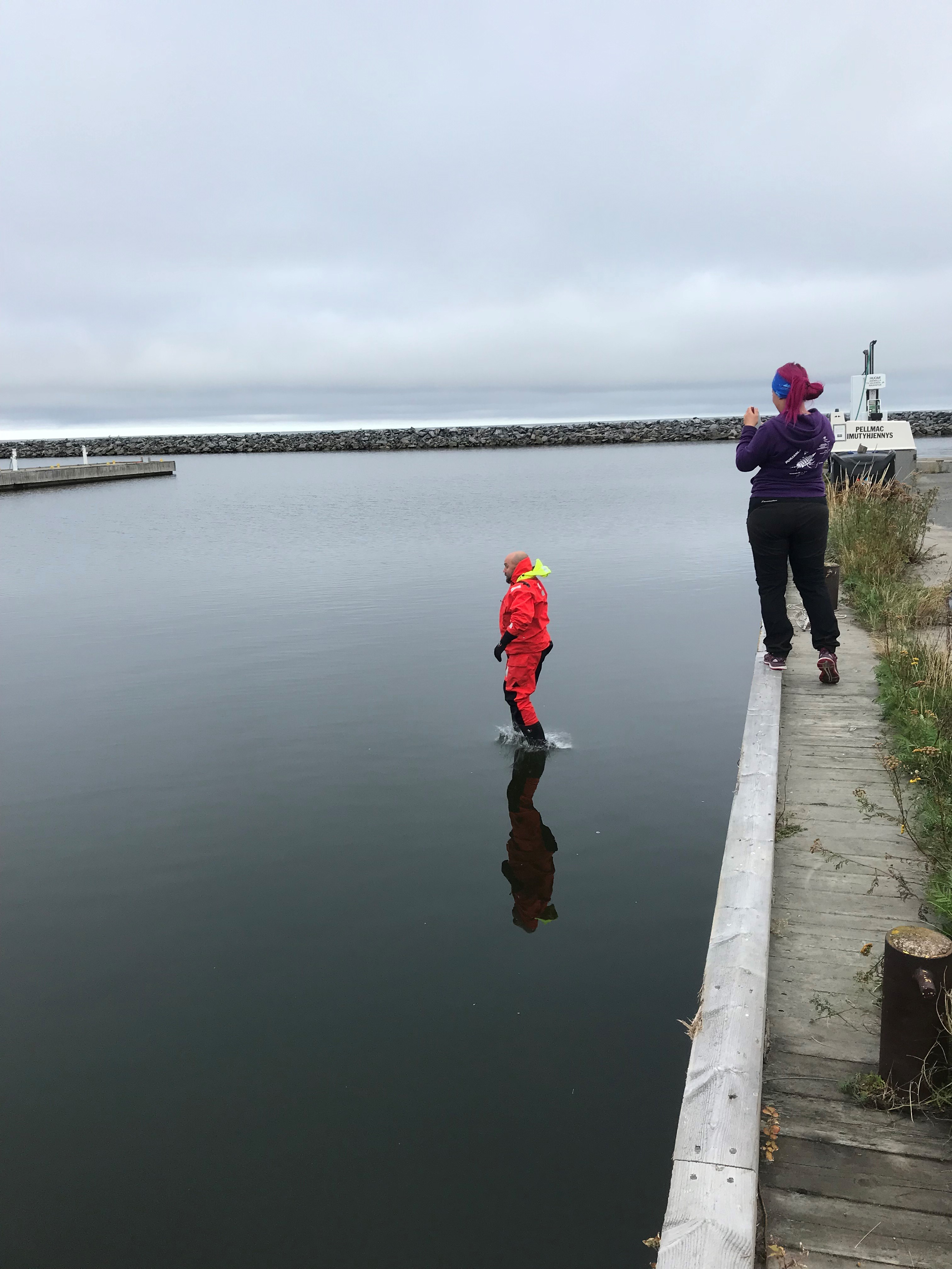 A teacher jumping in the water in survival suit, while Suvi Saarnio is watching on the jetty.