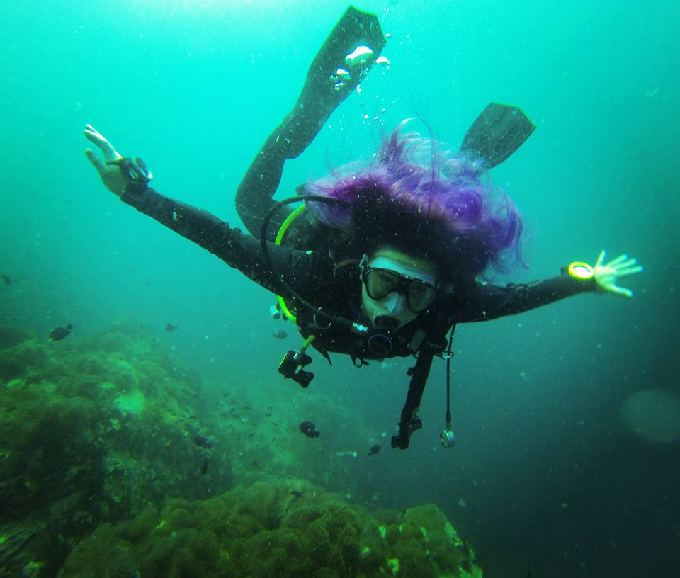 Suvi diving. Under her there is some reef and fishes.