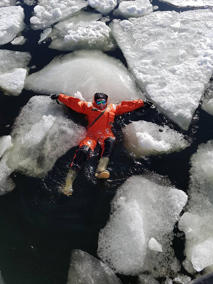 Suvi in the water with huge ice blocks around her. Dressed in a survival suit.