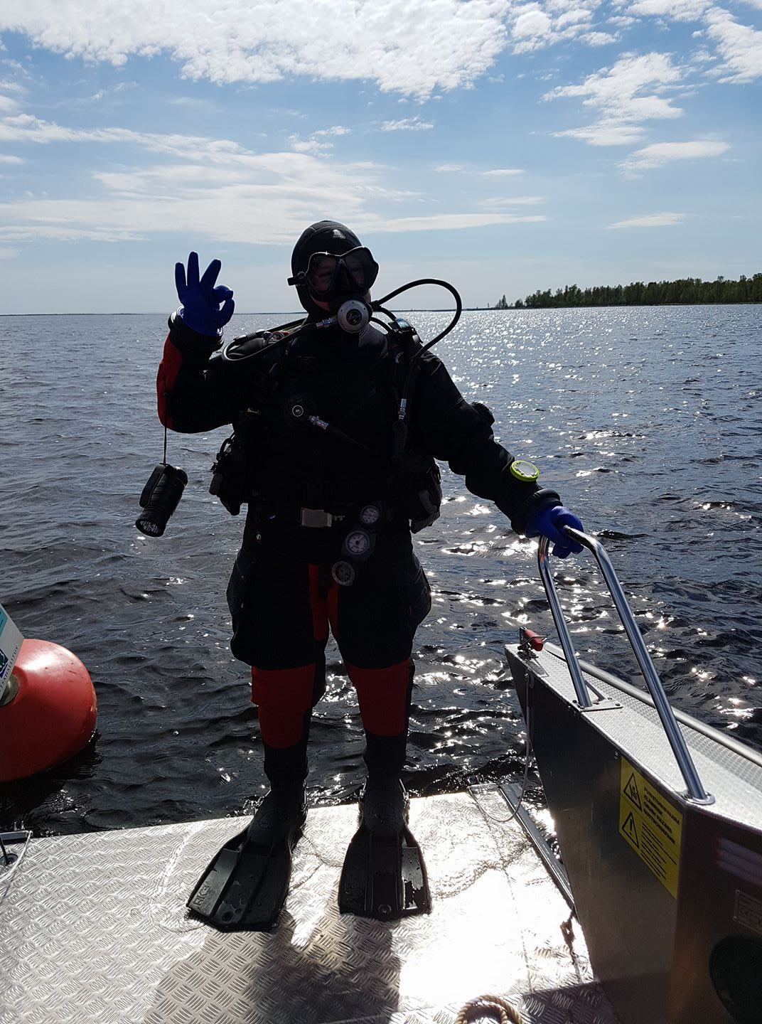 Suvi in diving suit, showing an ok sign.