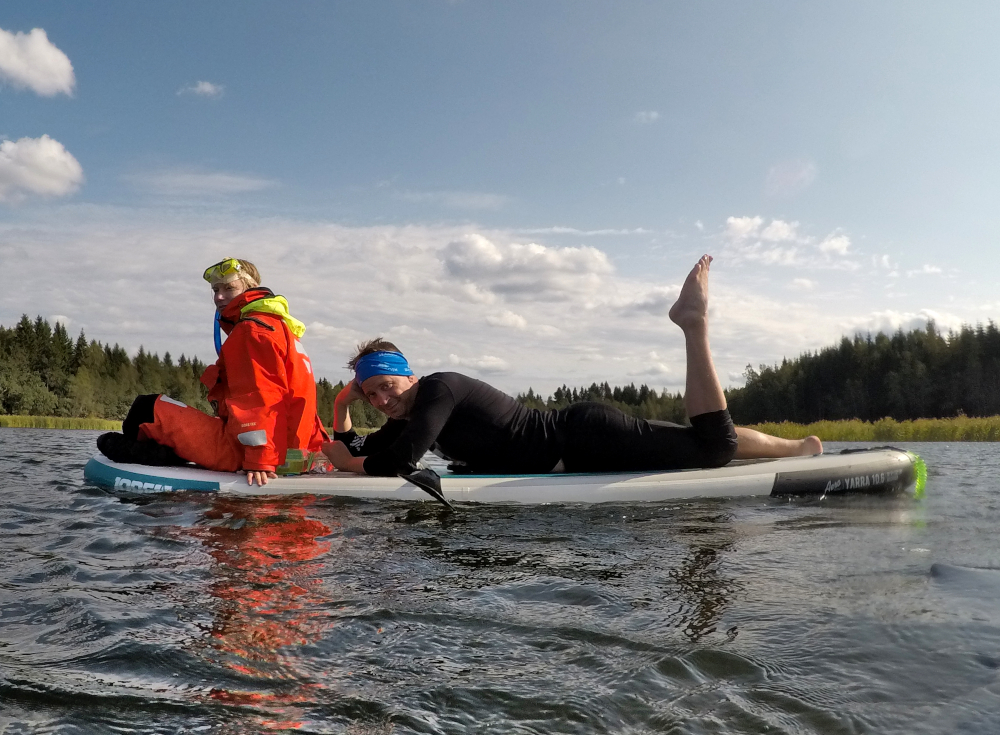 Jaakko laying on a SUP-board, one leg up. Very elegant. Other person is sitting at the bow of the board.