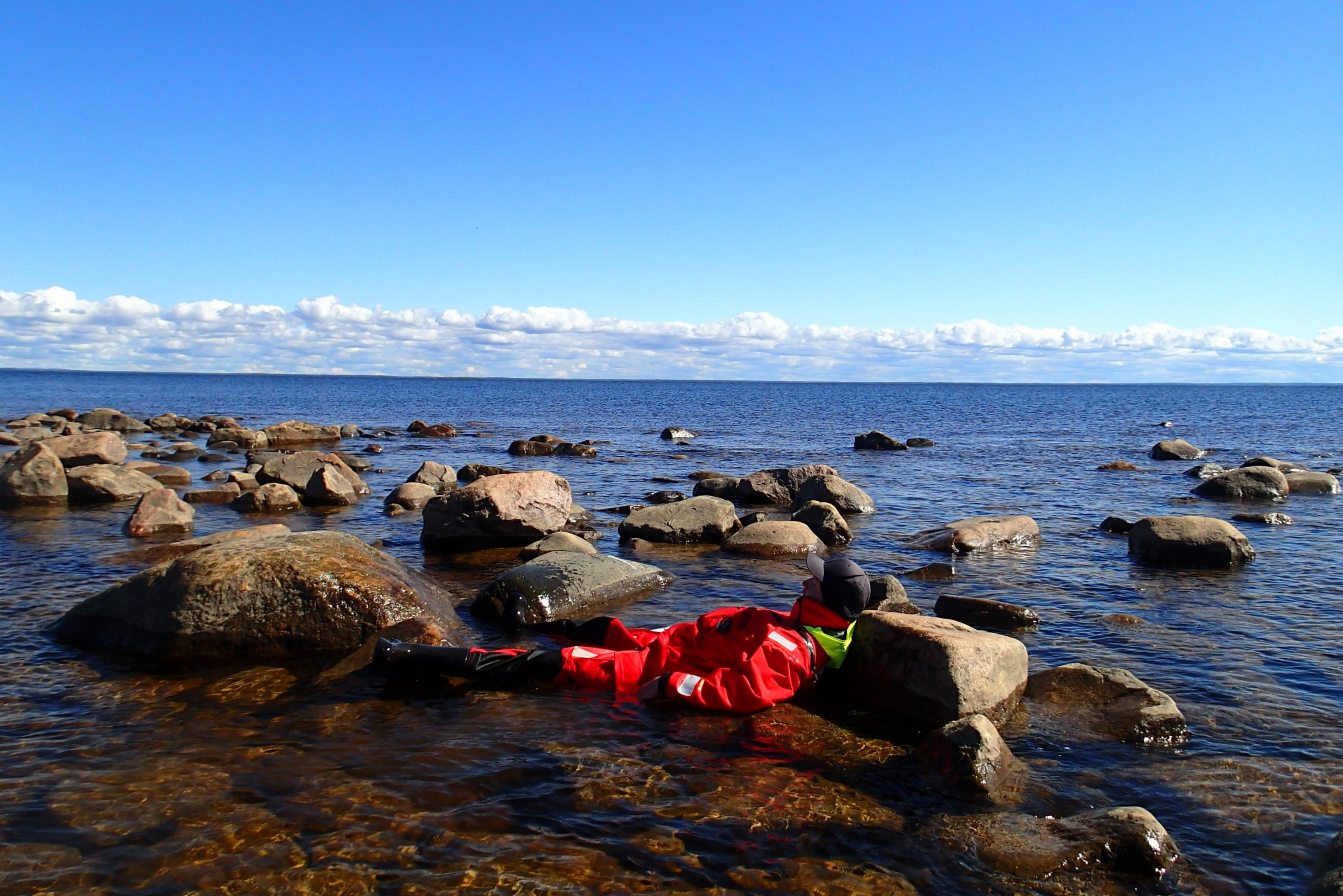A person laying on a shallow water between big rocks.