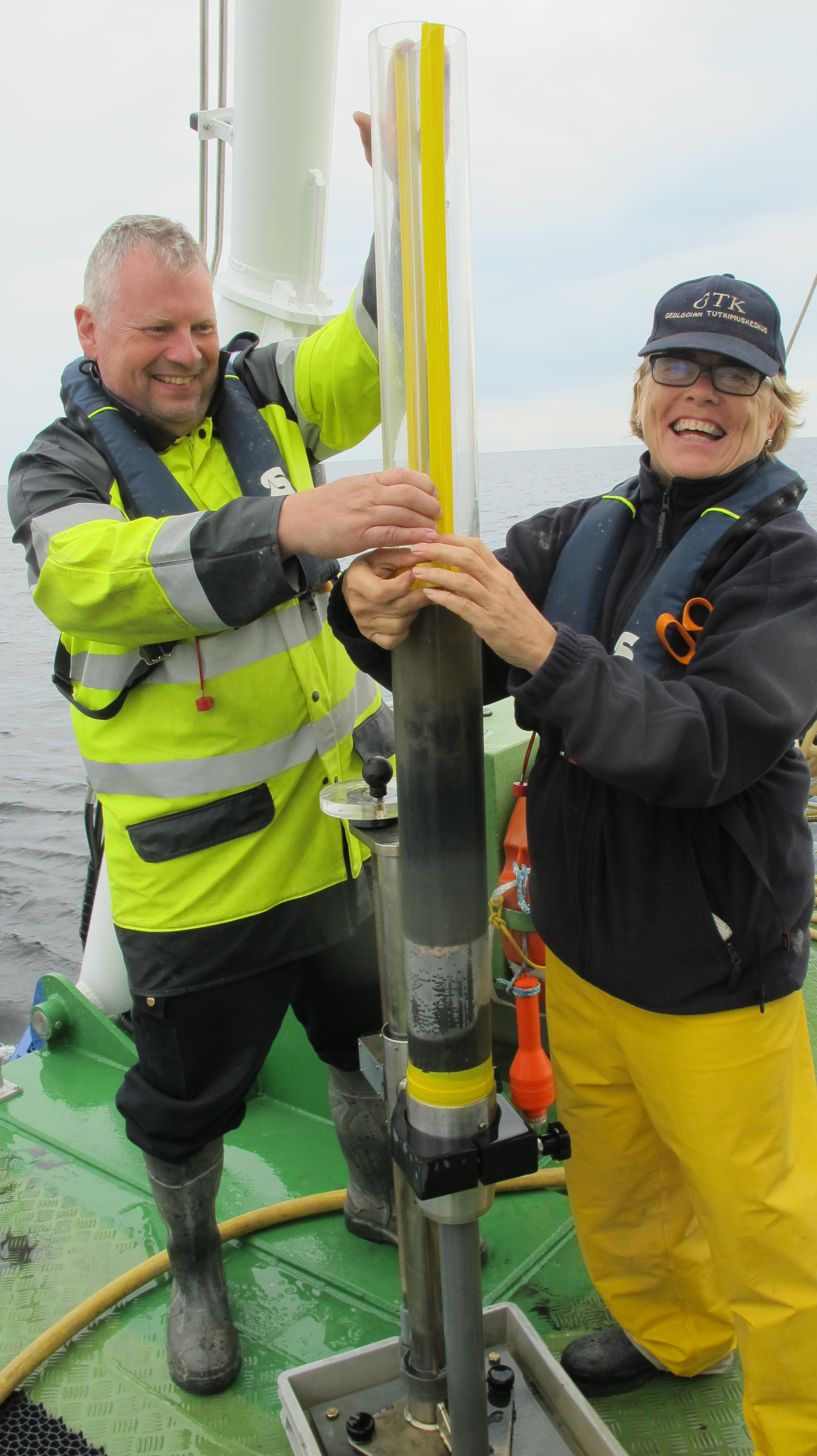 2 persons holding a sample tube on the deck.