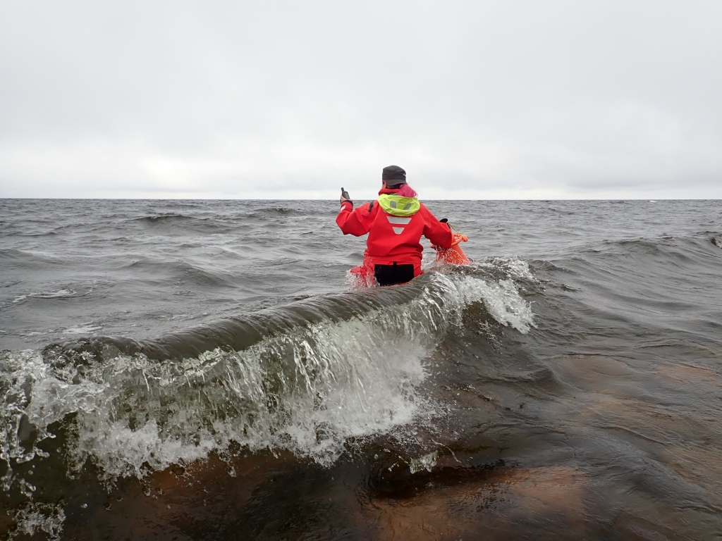Suvi walking on high waves in survival suit.