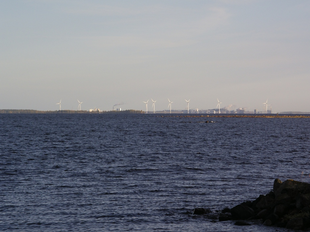 Sea and 8 wind mils on the shore. Behind them is industrial activity and air pollutants.