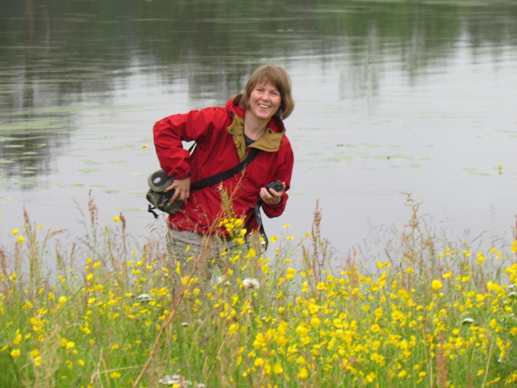 Merja Lipponen on the field. Behind her is water and in front of her a meadow of flowers.