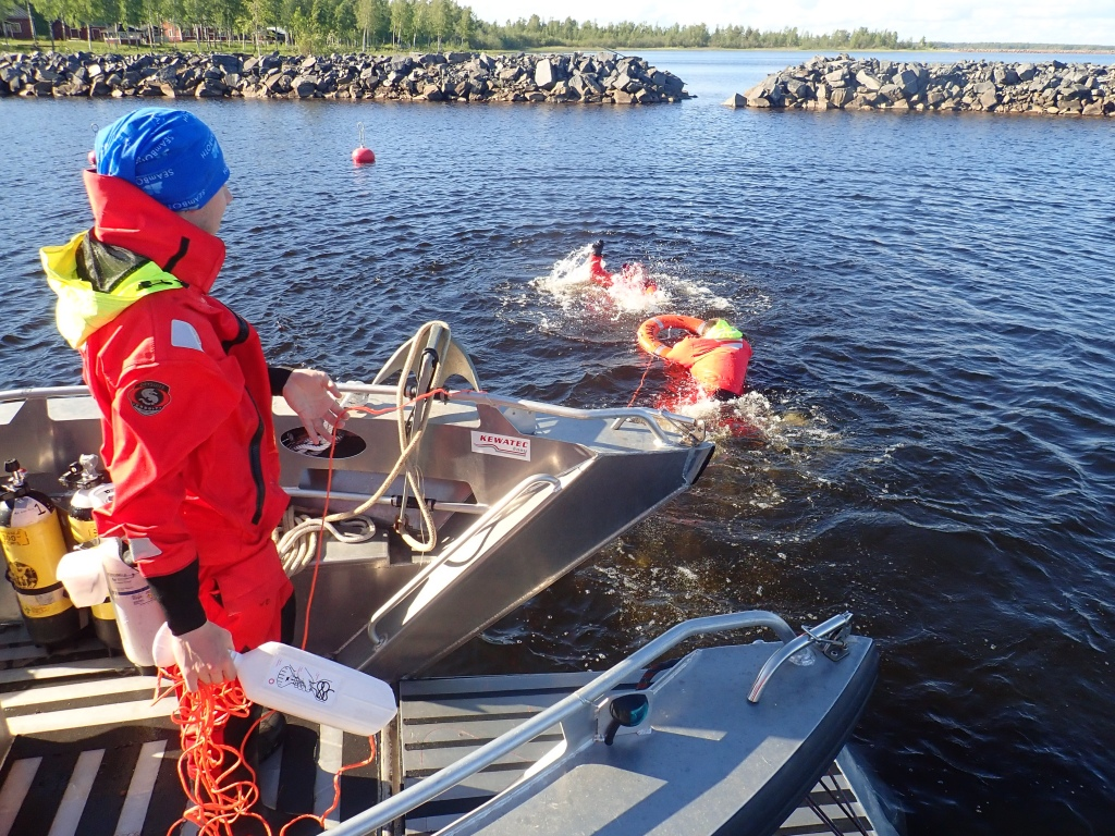 One person is pretending to drown on water and one is taking a safe-buoy to him. One person is standing on a dock and holding the safe-buoy's line.