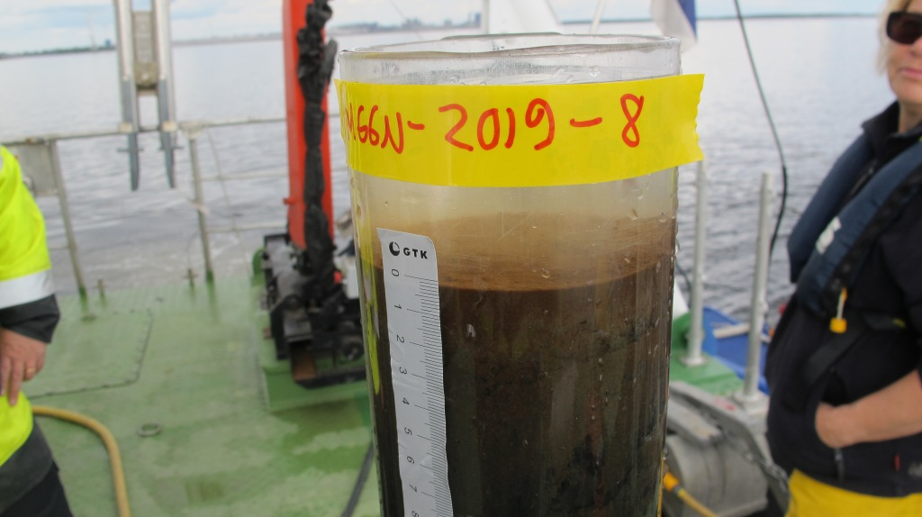 Sediment sample on the deck in see-through container.