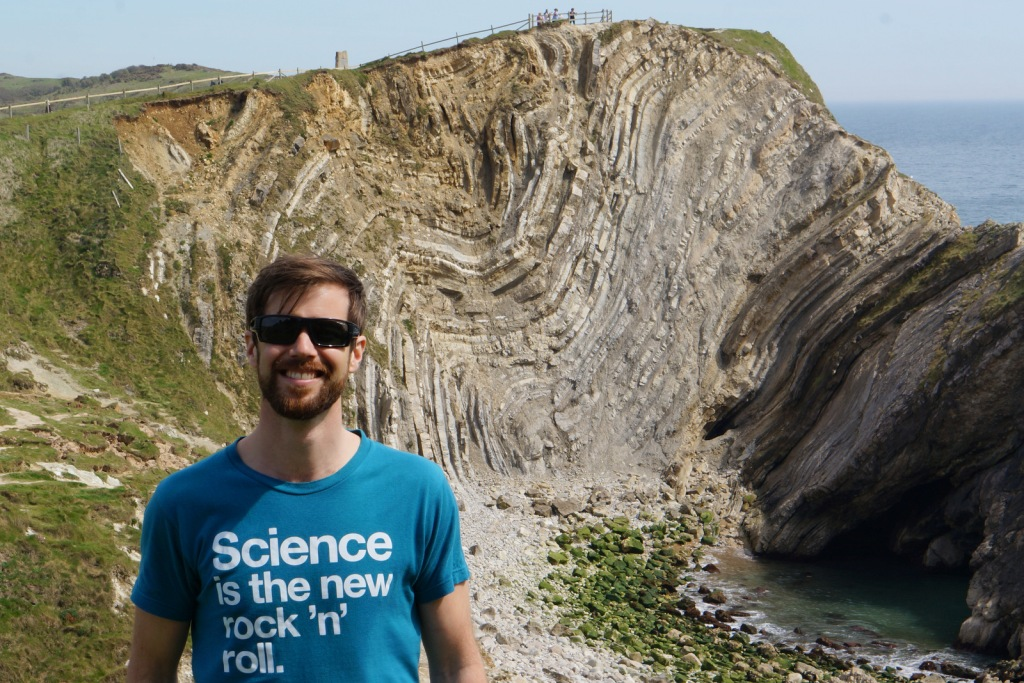"Gustav Kågesten in a t-shirt that says ""Science is the new rock 'n' roll"". Background is a amazing hill, with visible layers."