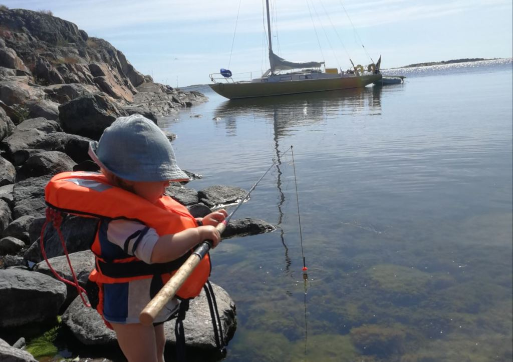 A small boy with big life vest and fishing pole standing on a rocky shore. A boat on the background.