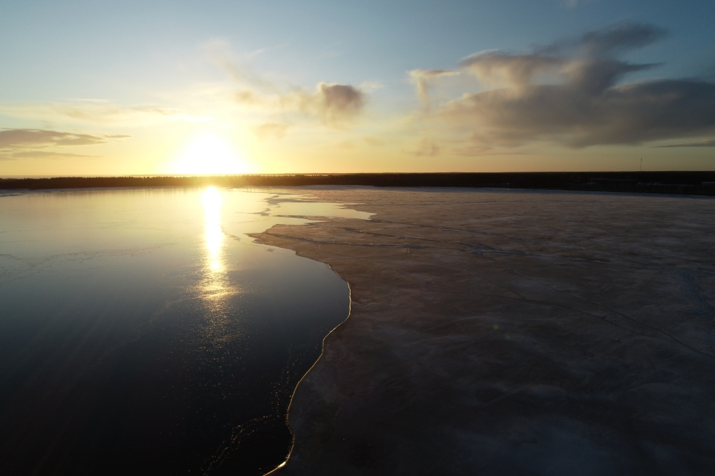 Very thin sea ice and open sea. Sun is setting.