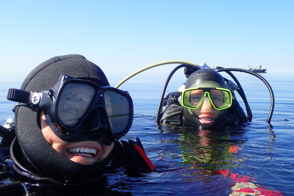 Two fully equipped divers on water.