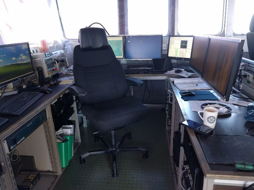 Office inside the ship. One chair and 6 monitors.