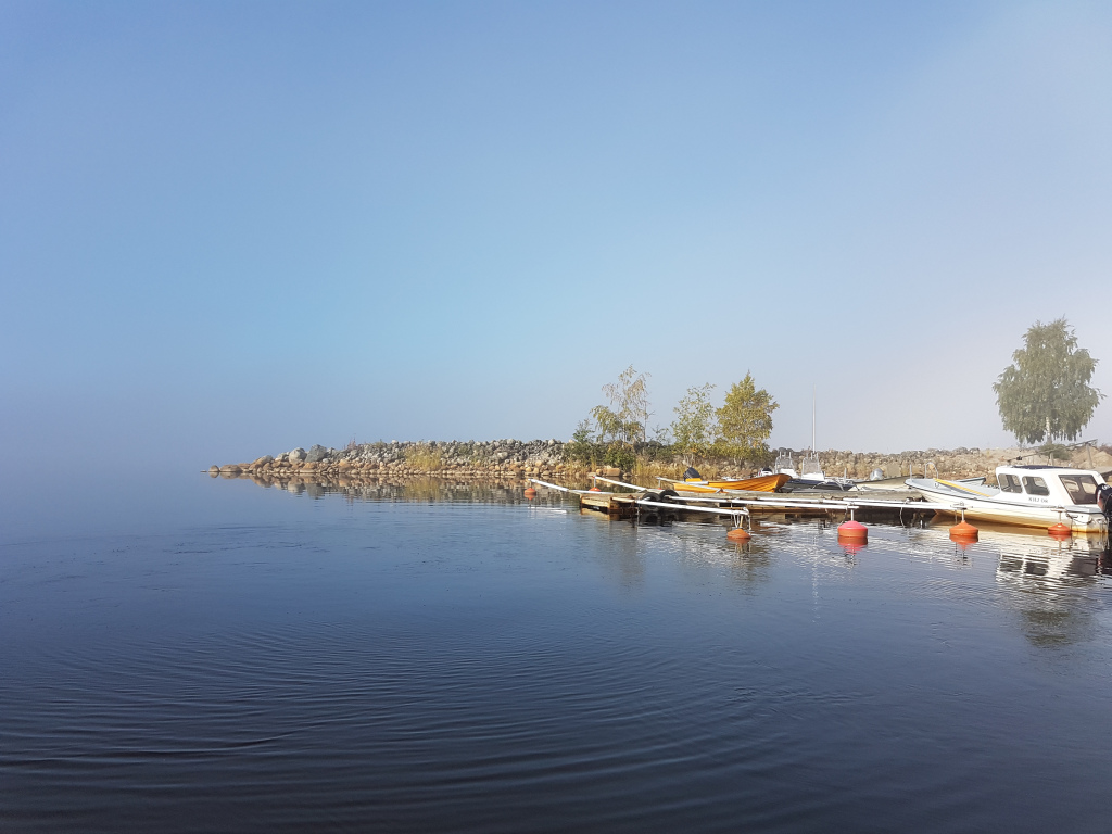Very still waters at a small harbour. There are 3 boats parked.
