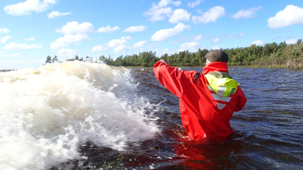 A person standing in hip deep water in a dry suit is about to get hit by a wave.