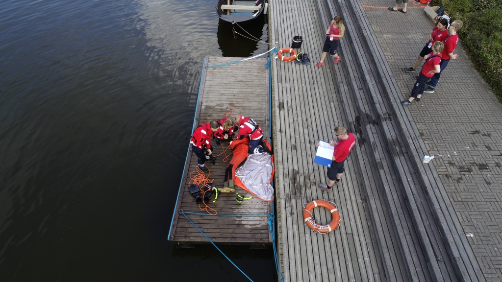 People practicing emergency help skills on a dock. One is taking notes.