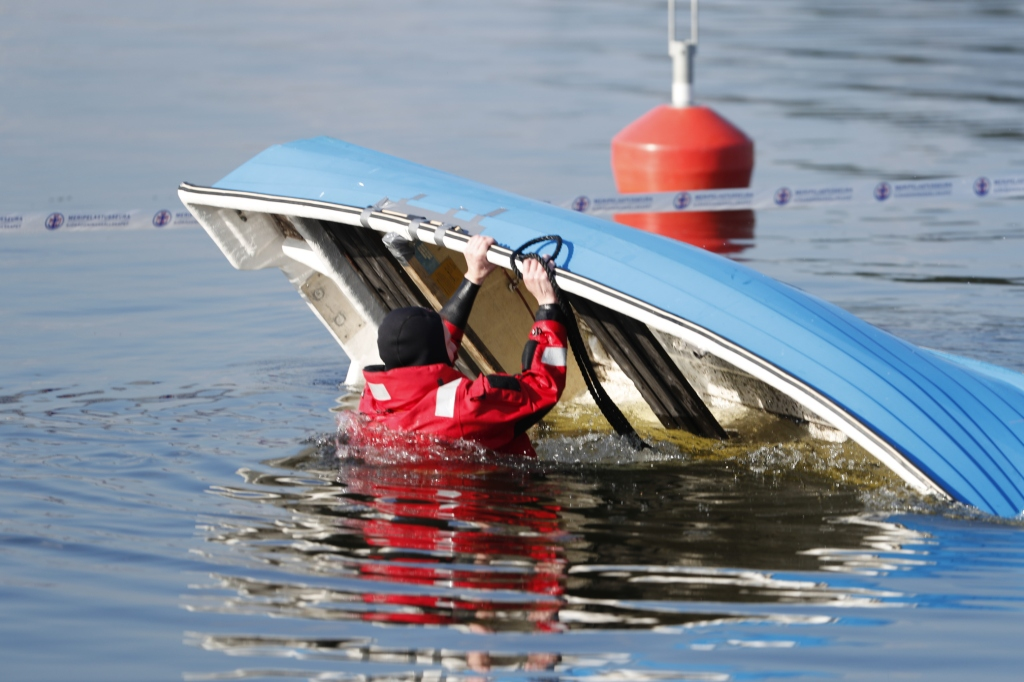 A person in survival suit in water, trying to turn around a boat.