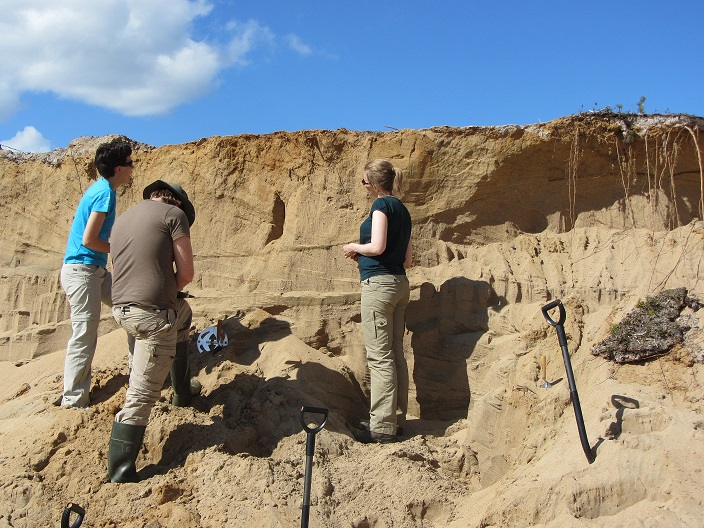 3 people standing in a sand pit, two shovels waiting by.