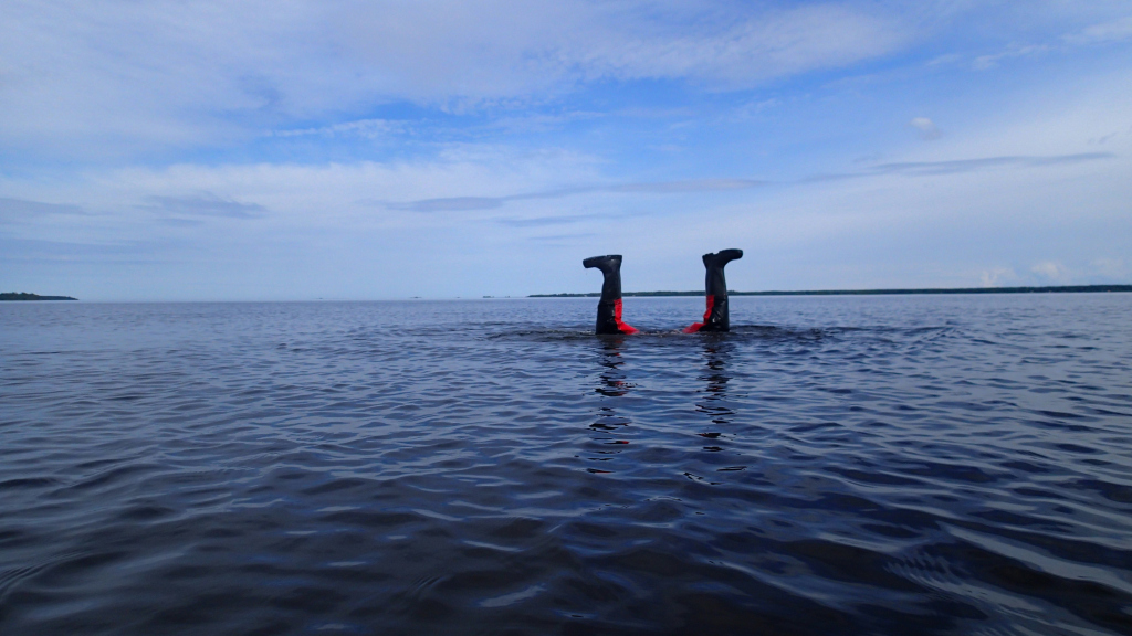 Person standing on his hands in water, legs up in the air, above the surface.