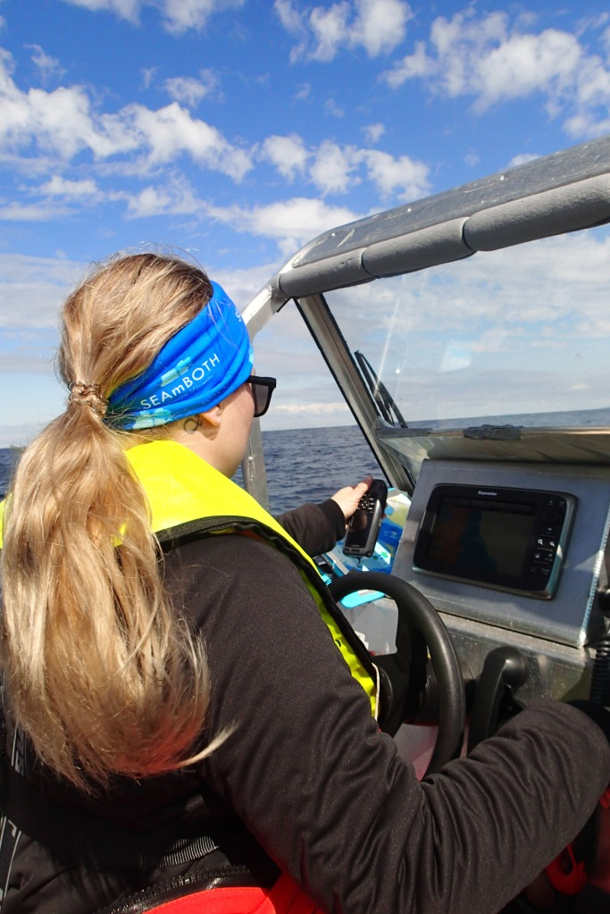 Suvi Saarnio driving a boat and looking at a GPS device.