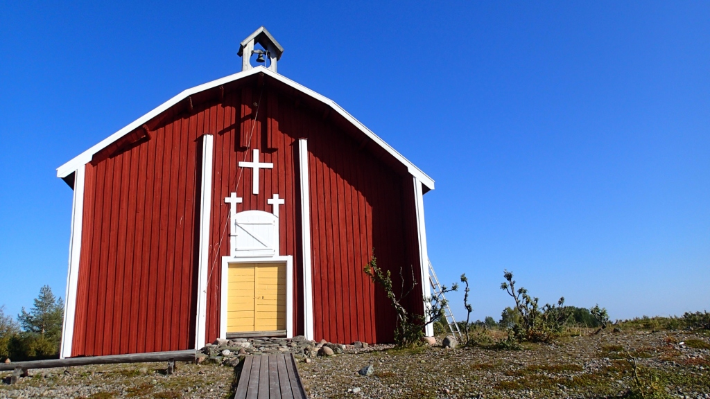 The red wooden church, looks like a barn.