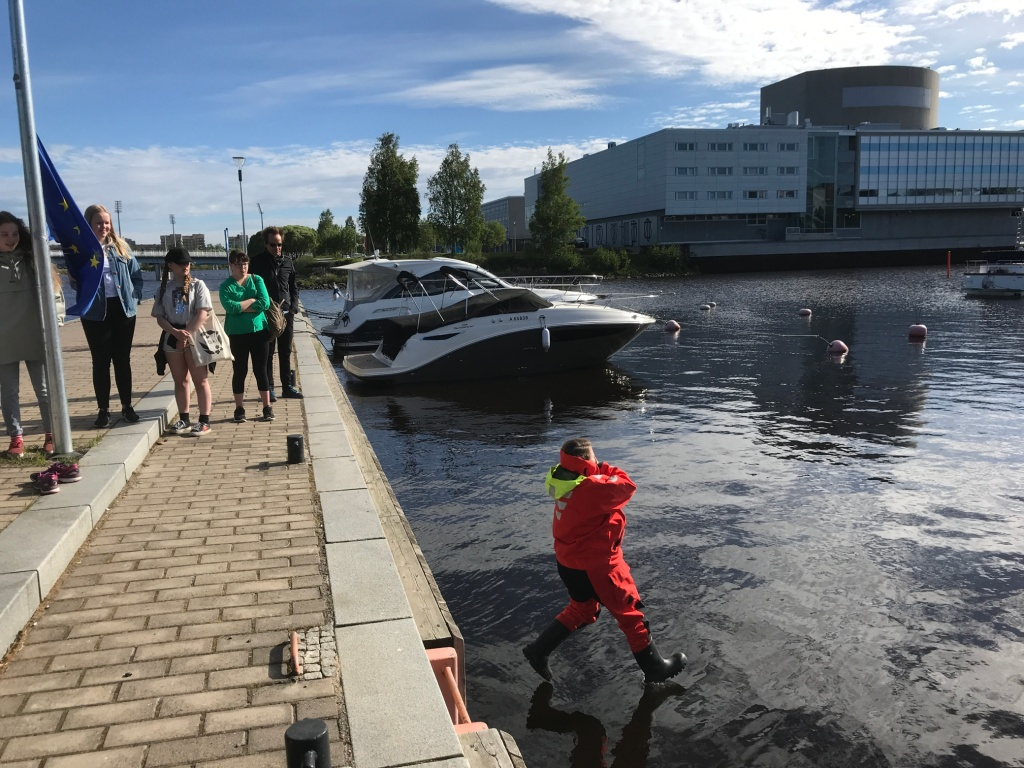 5 people on a jetty, watching when one is jumping in the water. Oulu's theater on the background.