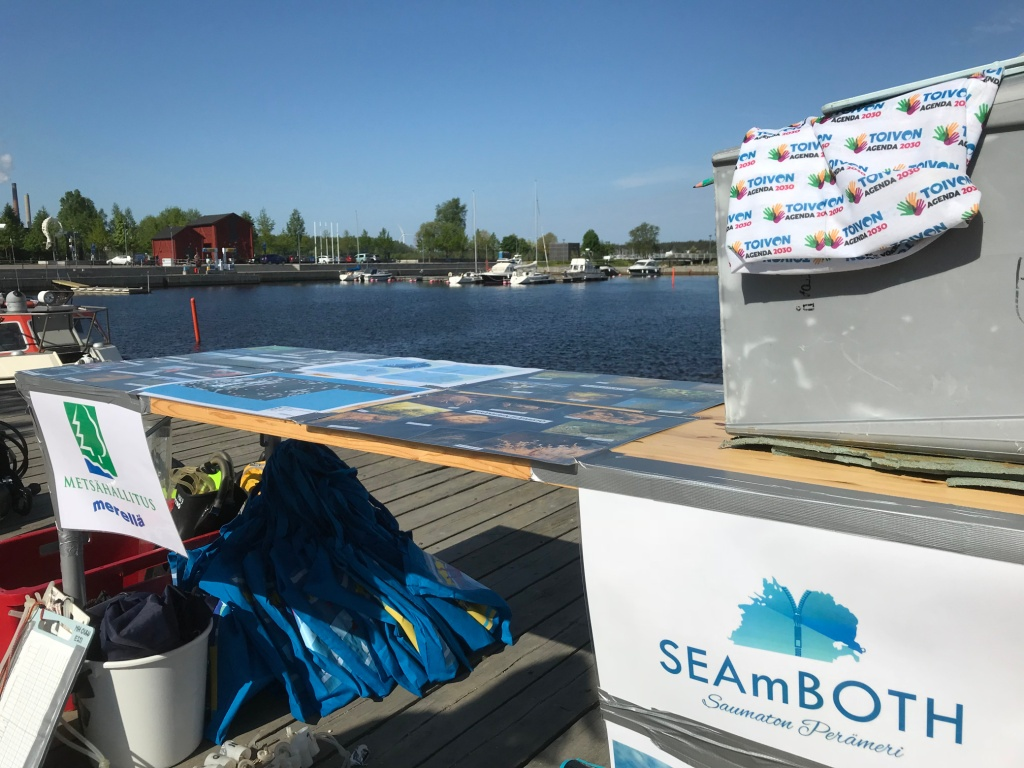 An event table on a jetty on sunny day. There are some SEAmBOTH materials on the table and diving gears next to it.