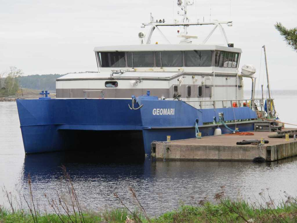 A catamaran named Geomari at a dock.