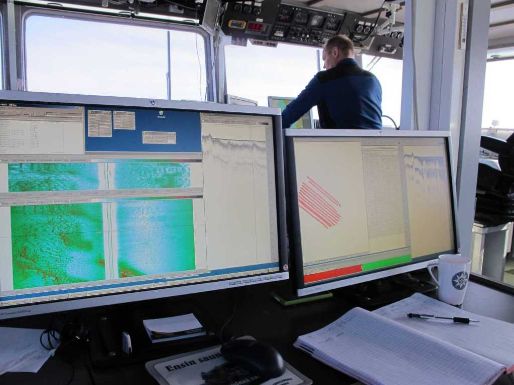 Inside the ship. Two screens showing depth data. A pilot on a background.