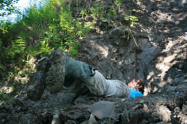 Outi Hyttinen in a clay pit, boots sticking out.