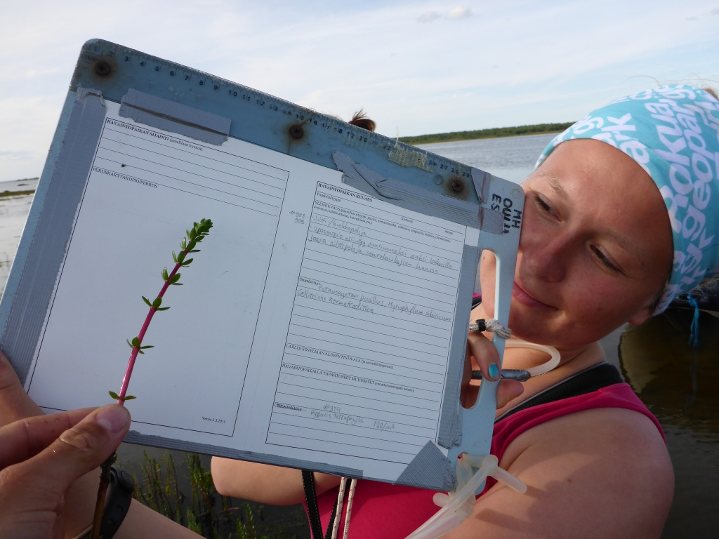 A woman is holding a plant and a cutting board with the data sheet taped to it.
