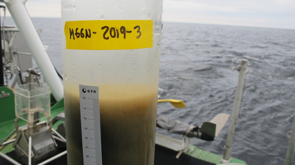 A clear plastic tube with soft sediment at the bottom, on board a research vessel