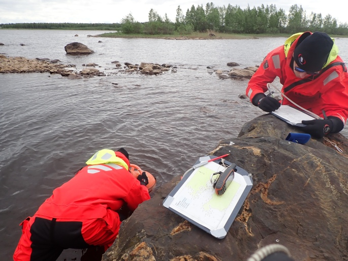 Two people doing field inventory in shallow sea